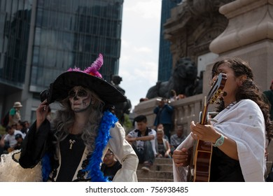 MEXICO CITY, MEXICO - OCTOBER 22, 2017: Mexican woman dressed up as a colorful skeleton for the Day of the Dead celebration; fake eyelashes, face paint and crown of flowers