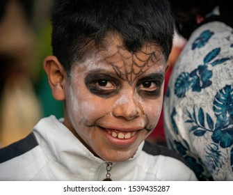 Mexico City / Mexico - October 25, 2018: A young boy with a painted face smiles at the camera for the Dia De Los Muertos celebration in Mexico.