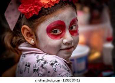 Mexico City, Mexico, October 31, 2018: A young girl shows off her painted face for Dia De Los Muertos in Mexico.