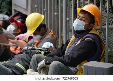 Mexico city, Mexico - September 21Th, 2017: Exhausted workers resting on the street after helping after Mexico city earthquake