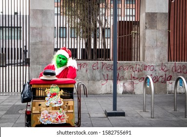 MEXICO CITY/MEXICO - DECEMBER 25, 2018: Man Dressed as Grinch in Santa Costume Playing Organ Grinder for Money on Christmas Day on Streets of Mexico City
