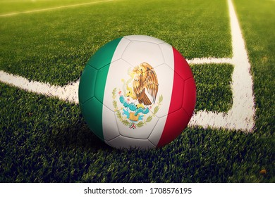 Mexico flag on ball at corner kick position, soccer field background. National football theme on green grass.