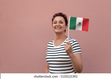 Mexico flag. Woman holding Mexican flag. Nice portrait of middle aged lady 40 50 years old with a national flag over pink wall background on the street outdoors.