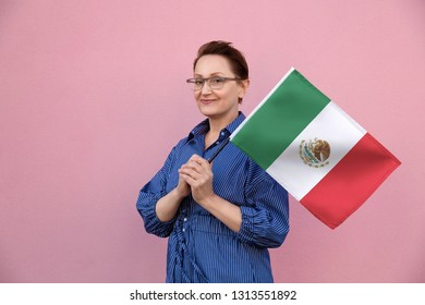 Mexico flag. Woman holding Mexican flag. Nice portrait of middle aged lady 40 50 years old holding a large flag over pink wall background on the street outdoors.