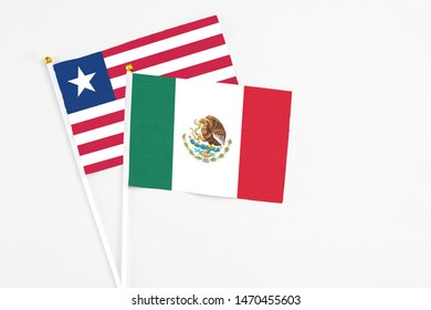 Mexico and Liberia stick flags on white background. High quality fabric, miniature national flag. Peaceful global concept.White floor for copy space.