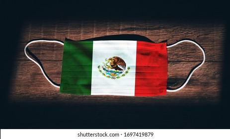 Bandera Nacional de México en máscara médica, quirúrgica, protectora sobre fondo de madera negra. Coronavirus Covid-19, Prevenir la infección, la enfermedad o la gripe. Estado de emergencia, bloqueo...