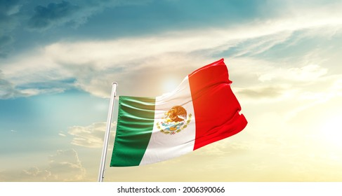 Mexico national flag waving in beautiful clouds.