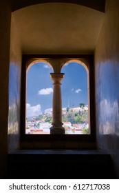 Mexico Oaxaca Santo Domingo monastery view from window with column to town and clouds