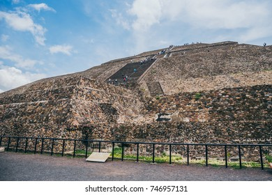 MEXICO - SEPTEMBER 21: People climbing the Pyramid of the Sun on a cloudy day with blue sky, September 21, 2017 in Teotihuacan, Mexico