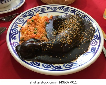 Mexico traditional cuisine mole poblano with chicken leg and vapored rice