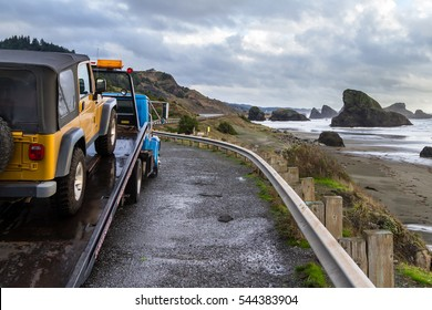 Meyers Beach, Oregon - October 27: Flat bed tow truck loading a broken vehicle with a beautiful coastal landscape in the background. October 27 2016, Meyers Beach, Oregon.