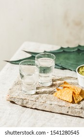 Mezcal or Mescal is a Mexican distilled alcoholic beverage made from any type of oven-cooked agave. With tortilla chips and guacamole dip.
