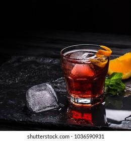 Mezcal Negroni cocktail. Italian aperitivo. Citrus peel. Ice.