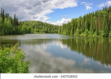 "MEZHDURECHENSK, RUSSIA - Beautiful view on the forest lake with reflections of clouds and tall pine trees at sanatorium ""Romantika"" (Romance), in the most picturesque place of Mountain Shoria."