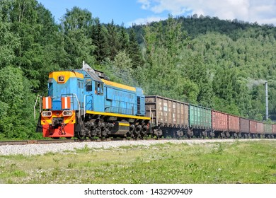 "MEZHDURECHENSK, RUSSIA - Colorful diesel locomotive with empty freight train running through the mountains to load coal in the largest underground mine in Russia named ""Raspadskaya""."