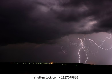 A mezocyclone lightning storm with dark clouds forming over a small town in Tornado Alley, Oklahoma at night