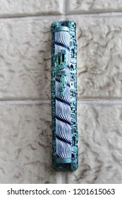 Mezuzah. Mezuzah is a decorative contained where Jews are placed inscribed with Hebrew verses from the Torah. Mezuzah from Israel