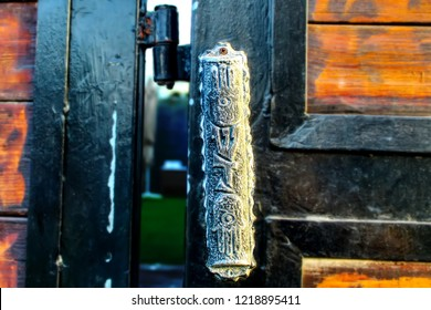 Mezuzah. Jewish traditions and customs: Jewish Religious attribute at the entrance to a house. Large vintage Mezuzah on wooden and metal gates in Israel. Jewish traditions and customs: Jewish Religio