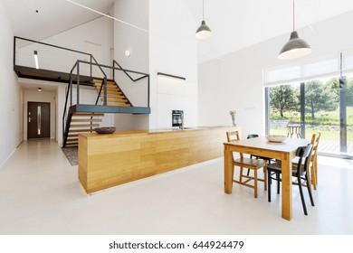 Mezzanine floor in minimalist spacious apartment with wooden details