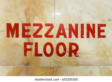 Mezzanine floor sign written in red letters on marble wall
