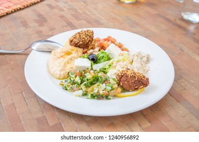 mezze or meze, selection of typical Arabic appetizers (hummus, falafel, baba ghanoush, Feta cheese, Marrakesh salad, tabule, olives) on a white dish with spoon on table