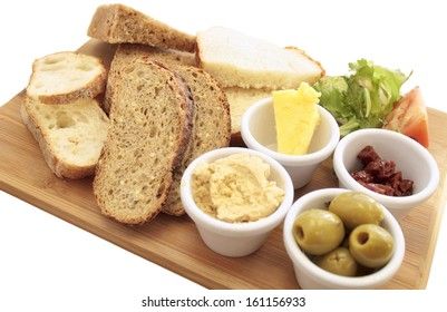 mezze of a variety of artisan breads on a wooden board, with green olives, sun dried tomatoes, hummus, and butter.The board is isolated on white with a clipping path.