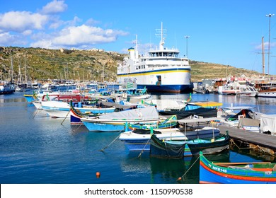 MGARR, GOZO, MALTA - APRIL 3, 2017 - Colourful traditional Maltese Dghajsa fishing boat moored in the harbour with the Gozo ferry moored in the port to the rear, Mgarr, Gozo, Malta, Europe.