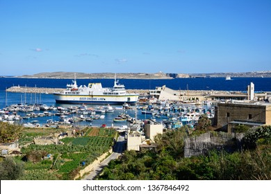 MGARR, GOZO, MALTA - APRIL 3, 2017 - Fishing boats and yachts moored in the harbour with the Gozo ferry in the port to the rear and fields in the foreground, Mgarr, Gozo, Malta, April 3, 2017.