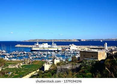 MGARR, GOZO, MALTA - APRIL 3, 2017 - Fishing boats and yachts moored in the harbour with the Gozo ferry moored in the port to the rear, Mgarr, Gozo, Malta, Europe, April 3, 2017.