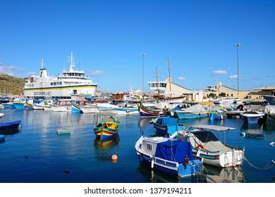 MGARR, GOZO, MALTA - APRIL 3, 2017 - Colourful traditional Maltese Dghajsa fishing boat moored in the harbour with the Gozo ferry moored in the port to the rear, Mgarr, Gozo, Malta, April 3, 2017.