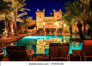 M'hamid, Morocco - February 22, 2016: view of pool bar in Chez le Pacha hotel with typical decoration with reflection in the poo and deck chairl in front