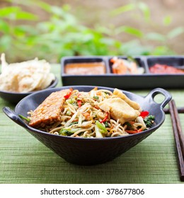 Mi goreng, mee goreng Indonesian cuisine, spicy stir fried noodles with tempeh and assortment of asian sauces Copy space