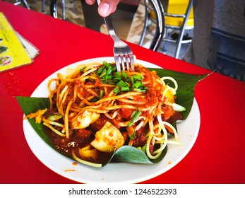 Mi goreng or mee goreng mamak, Indonesian and Malaysian cuisine, spicy fried noodles in a plate at a restaurant. Fresh hot with steamed smoke.