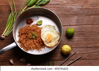 Mi goreng or mee goreng mamak, Indonesian and Malaysian cuisine, spicy fried noodles on wooden table.