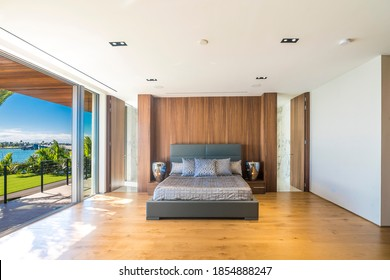 Miami Beach - April 2019: A modern bedroom with wood planks floors and minimalist design, with views of the bay.