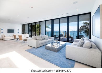 Miami Beach - April 2019:  Modern living area with wide views of the bay and city. Beautiful minimalist white interior with designer sofas.