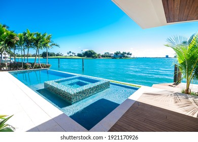 Miami Beach - April 2020: Luxury infinity pool and jacuzzi by a waterfront. Contemporary South Florida design.