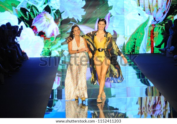 MIAMI BEACH, FL - JULY 14: Designer Sinesia Karol and model walks the runway for Sinesia Karol during the Paraiso Fashion Fair at The Paraiso Tent on July 14, 2018 in Miami Beach, Florida.