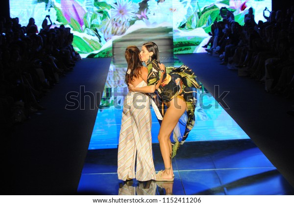 MIAMI BEACH, FL - JULY 14: Designer Sinesia Karol and model walks the runway for Sinesia Karol during the Paraiso Fashion Fair at The Paraiso Tent on July 14, 2018 in Miami Beach, Florida.