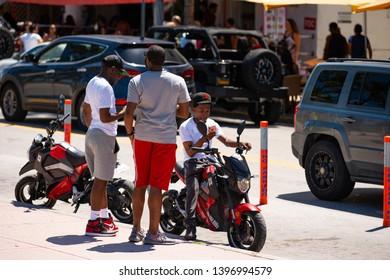 MIAMI BEACH, FL, USA - MAY 11, 2019: Young men on motorcycles texting at Ocean Drive Miami Beach FL