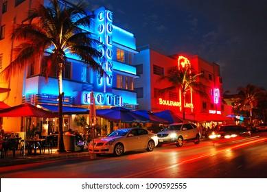Miami Beach, FL, USA November 20 Cars cruise past the bright neon lights and Art Deco buildings in Miami Beach, Florida