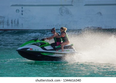 Miami Beach, FL, USA - October 10, 2016: A couple rides pwc (personal watercraft) or water scooter in Miami Beach.