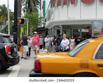 Miami Beach, Fla./USA-March 20, 2019: A yellow taxi rushes past a crowd of pedestrians waiting to cross Collins Avenue in the heart of the city's tourist district.