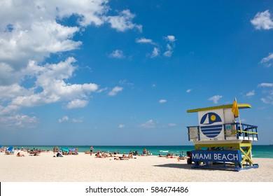 MIAMI BEACH, FLORIDA - FEBRUARY 15, 2017: Tourists sunbath on Miami Beach, Florida, USA, next to a colorfully painted lifeguard station on February 15, 2017.