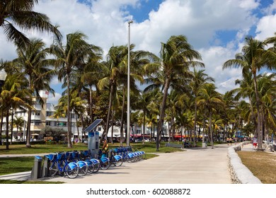 MIAMI BEACH, FLORIDA - FEBRUARY 15, 2017: Man uses a self service kiosk station to rent a bicycle on Ocean Drive in Miami Beach, Florida, USA on February 15, 2017.