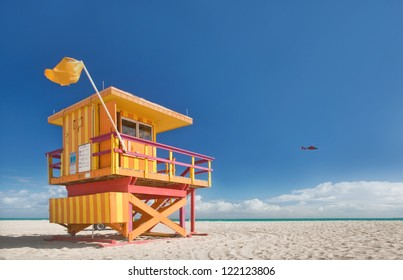 Miami Beach Florida, lifeguard house in a typical colorful Art Deco style on a bright sunny summer day, with blue sky and Atlantic Ocean in the background. World famous travel location.