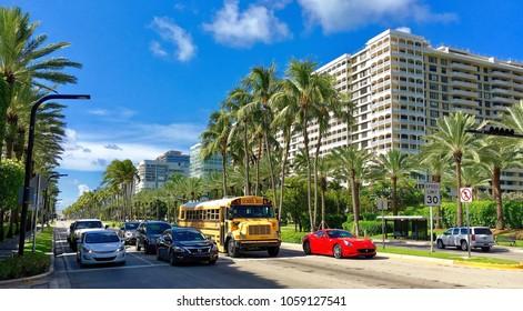 Miami beach, Florida, USA - July 18, 2016: Palms, school bus and sport car on Collins Avenue Surfside Miami South Beach