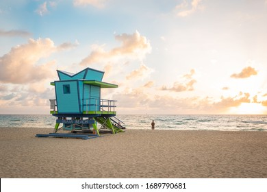 Miami Beach sunrise with lifeguard tower and coastline with colorful cloud and blue sky.