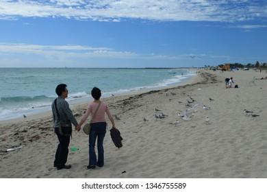 Miami Beach, USA - April 11 2008: The couple are enjoying the breeze along Miami Beach.
