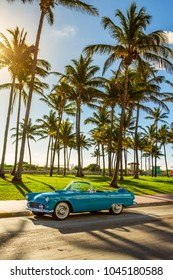Miami Beach / USA - February 16, 2018: A vintage convertible car parked on Ocean Drive next to the beach on a sunny day.